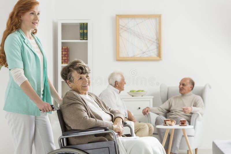 Infermiere che spinge signora in sedia a rotelle fotografia stock