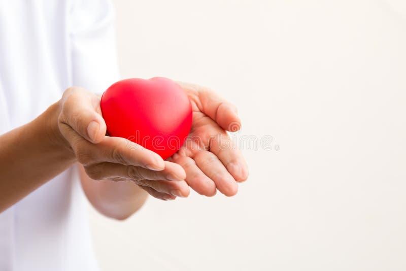 Infermiere che tiene cuore rosso in 2 mani immagine stock libera da diritti