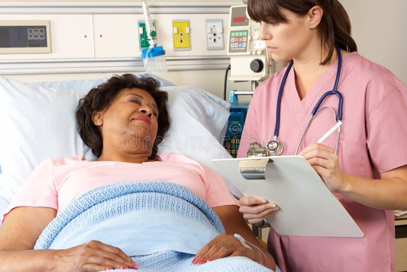 Infermiere che visualizza paziente femminile senior sul reparto fotografia stock libera da diritti