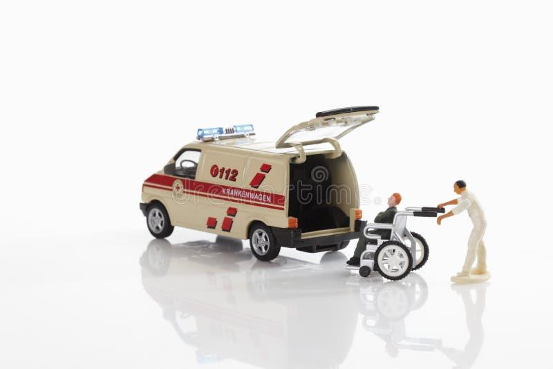 Infermiere con l'uomo su sedia a rotelle vicino all'ambulanza fotografia stock