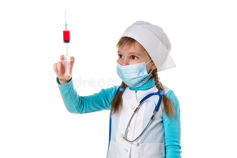 Infermiere con la maschera di protezione medica e una siringa con una droga, fondo bianco del paesaggio fotografia stock