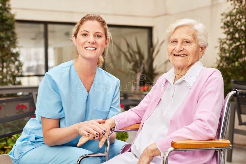 infermiere e donna senior in sedia a rotelle immagine stock libera da diritti