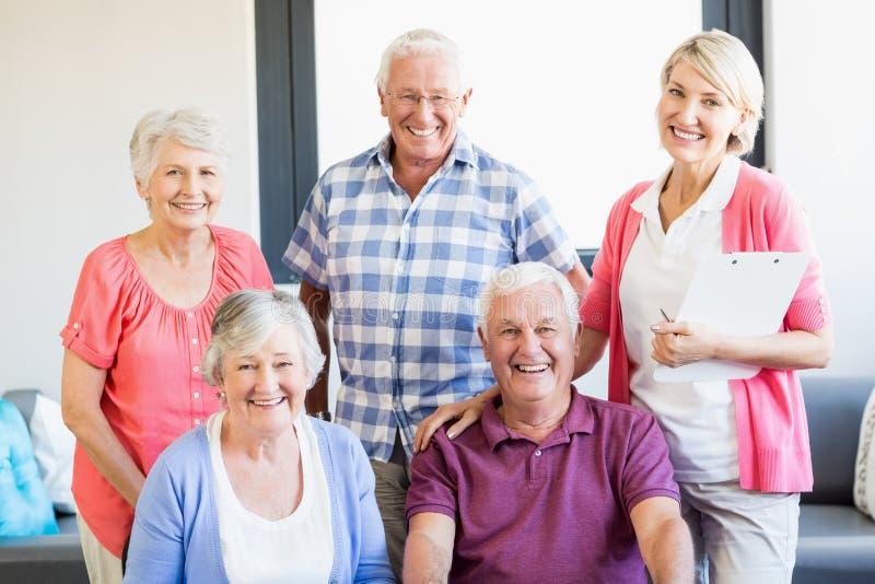 Infermiere ed anziani che stanno insieme immagini stock