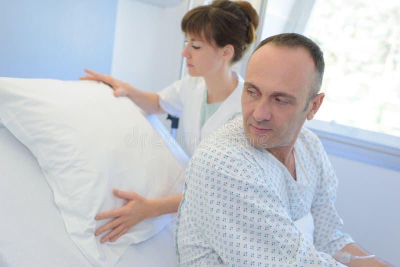 Infermiere femminile che assiste paziente in reparto all'ospedale immagine stock