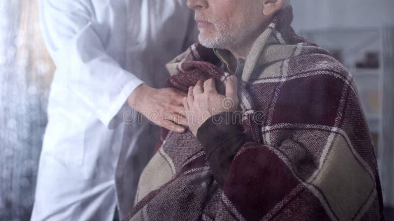 Infermiere femminile che copre paziente maschio di coperta, cura del centro ospedaliero, malattia di vecchiaia fotografie stock libere da diritti