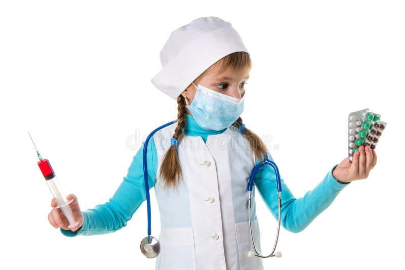 Infermiere femminile che indossa maschera medica che tiene la siringa e le pillole nelle mani, esaminanti i piatti delle pillole  immagini stock