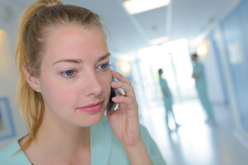 Infermiere femminile del ritratto che utilizza telefono cellulare nell'ospedale fotografia stock libera da diritti
