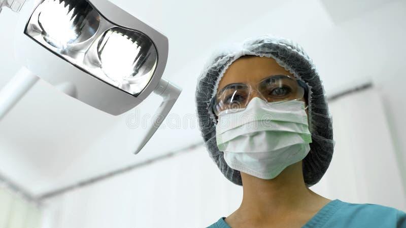 Infermiere femminile della chirurgia che esamina paziente, preparante per la procedura medica immagini stock
