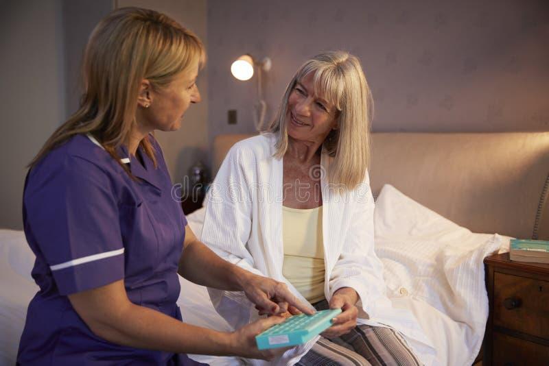 Infermiere Helping Senior Woman per organizzare farmaco sulla visita domestica fotografie stock