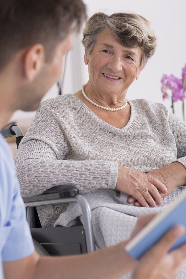 Infermiere maschio e donna più anziana su una sedia a rotelle immagini stock libere da diritti
