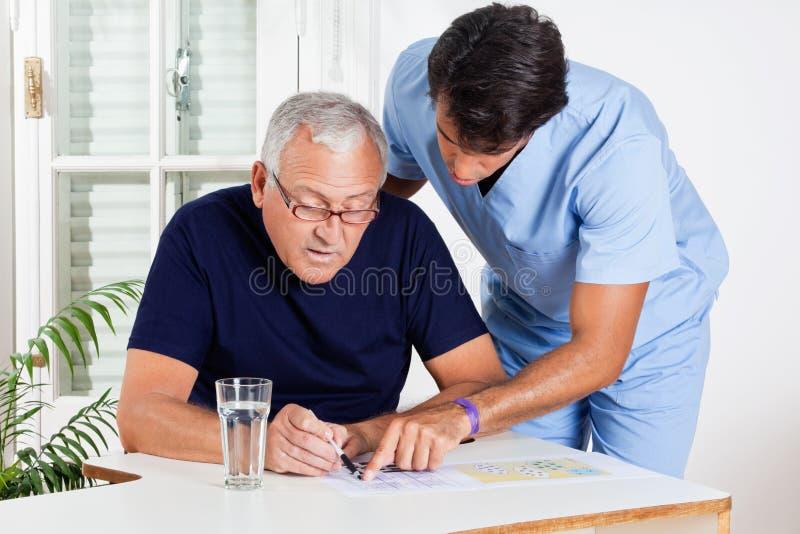 Infermiere maschio Helping Senior Man nella soluzione del puzzle immagini stock