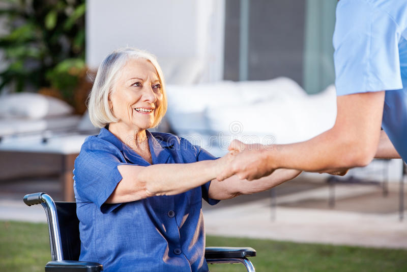 Infermiere maschio Helping Senior Woman da alzarsi da fotografie stock libere da diritti