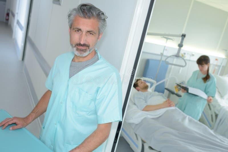 Infermiere maschio sicuro del ritratto con i colleghi che esaminano paziente fotografia stock libera da diritti