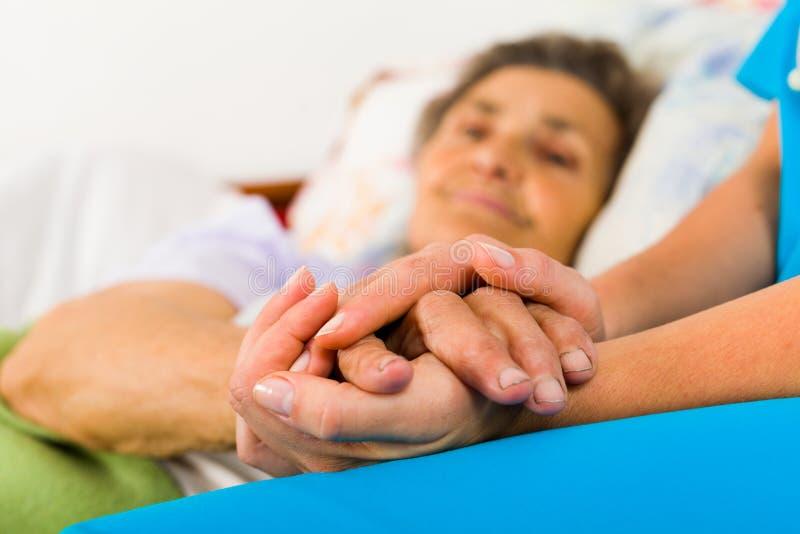 Infermiere preoccupantesi Holding Hands fotografie stock libere da diritti