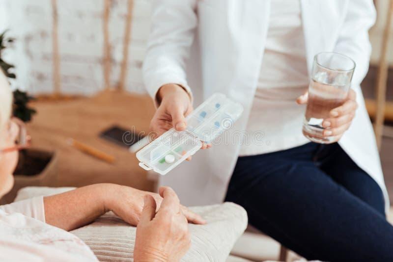 Infermiere preoccupantesi piacevole che dà le pillole ad una donna anziana fotografia stock libera da diritti