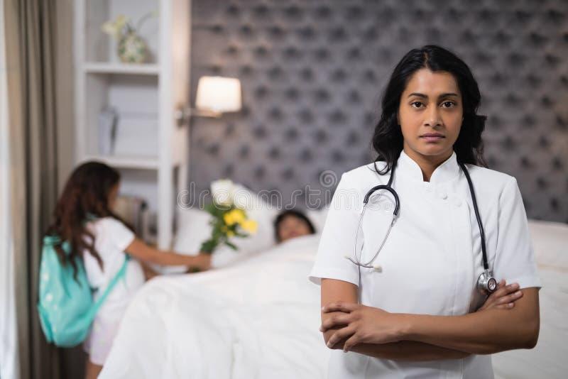 Infermiere serio che sta con il paziente sul letto a casa immagini stock libere da diritti