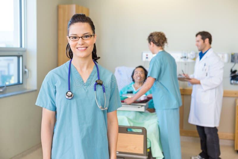 Infermiere Smiling With Patient e Team In medico fotografia stock libera da diritti
