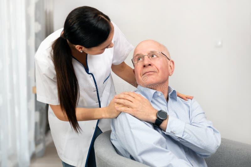 Infermiere sorridente e paziente anziano dell'uomo senior a casa fotografie stock libere da diritti