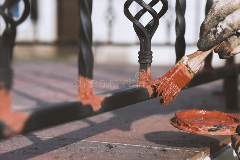 Inferriate forgiate di verniciatura sulle scale all'entrata della casa Protezione antiruggine fotografie stock