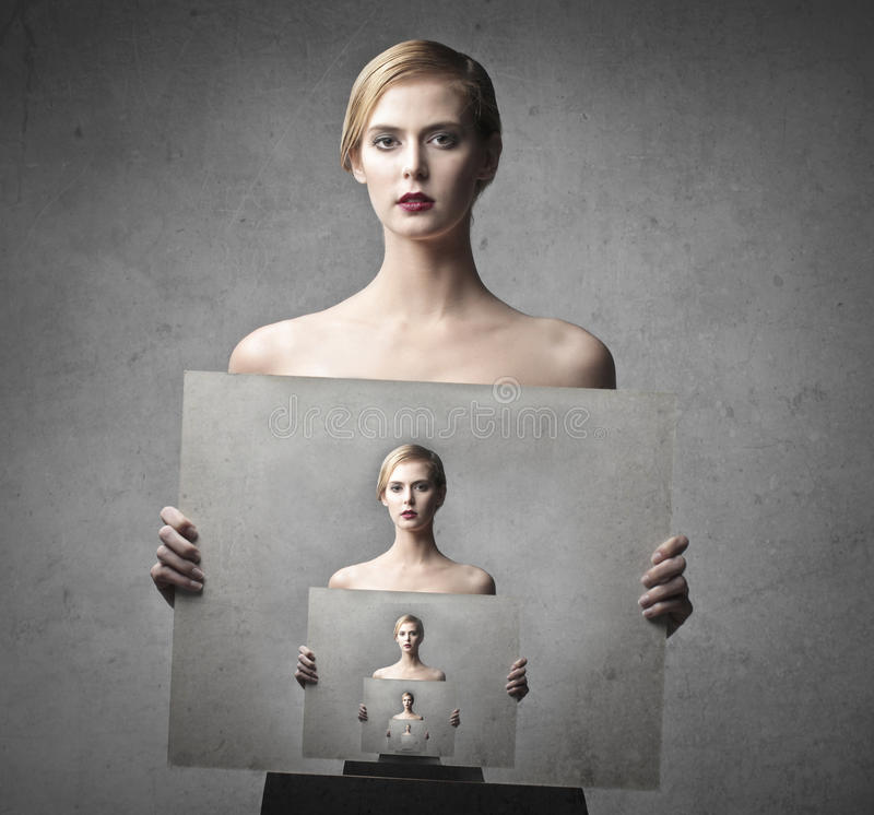 Infinite beauty. Beautiful woman holding a picture of herself holding a picture of herself as and infinite serie royalty free stock images
