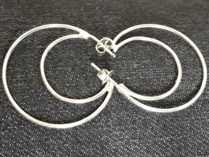 Infinite metal. Silver earrings in moon shape infinite metal stock photos