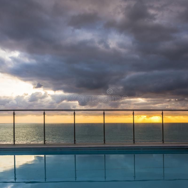 Infinite pool against a dramatic sky during sunset. Image of a lone tree against a beach and a dramatic sky during sunset stock image