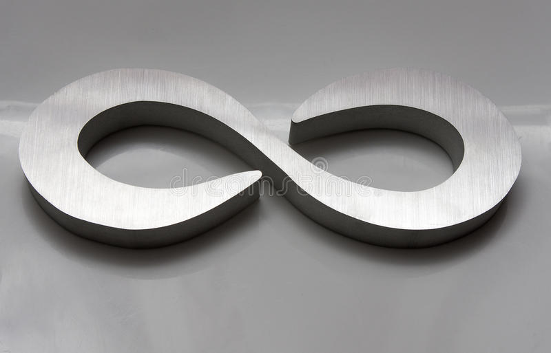 Infinity. Symbol machined out of aluminum on industrial CNC waterjet against grey background royalty free stock photography
