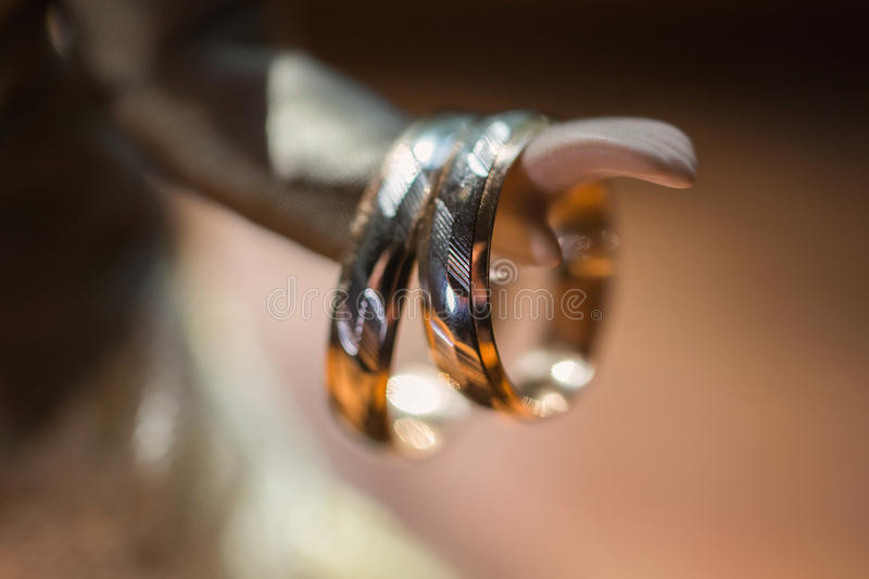 Infinity sign of the rings, wedding rings on a yellow background,wedding bands. On the hand of doll stock photography