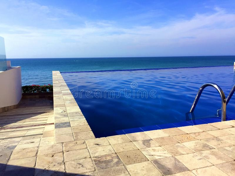 INFINITY SWIMMING POOL, COAST OF ECUADOR. Water flowing over the edge of this luxurious infinity pool producing a visual effect of water with no boundary and as stock photography