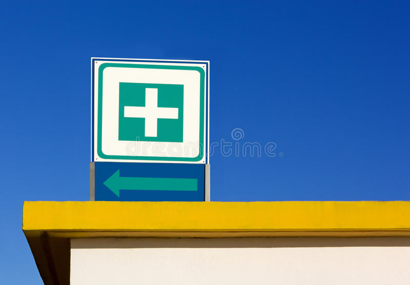 Infirmary Symbol Sign over a Roof. Infirmary symbol sign over a yellow colored roof stock image
