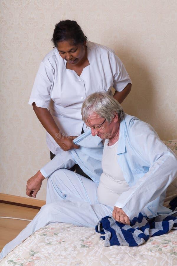 Infirmière aidant l'homme plus âgé obtenant habillé photo libre de droits
