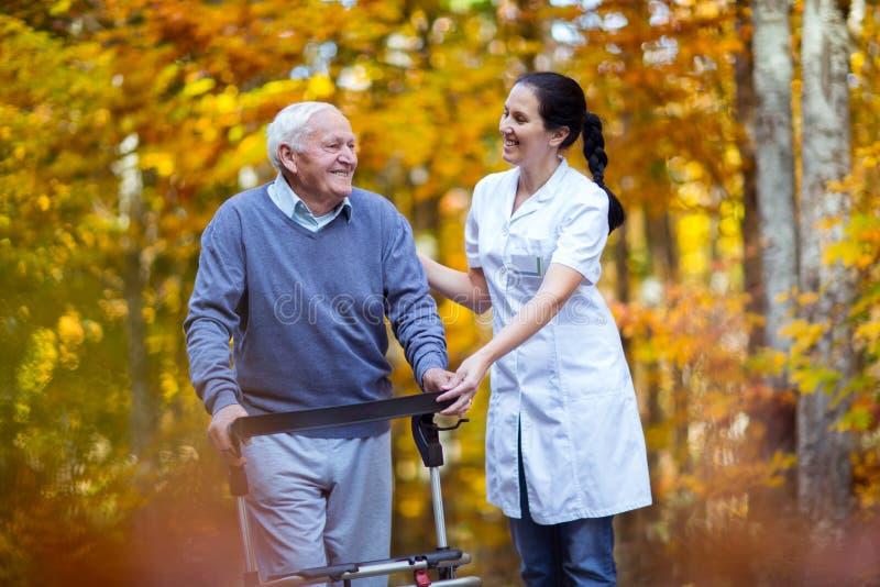 Infirmière aidant l'homme supérieur plus âgé photo stock