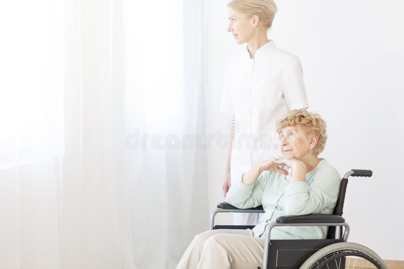 Infirmière aidant la femme supérieure images stock