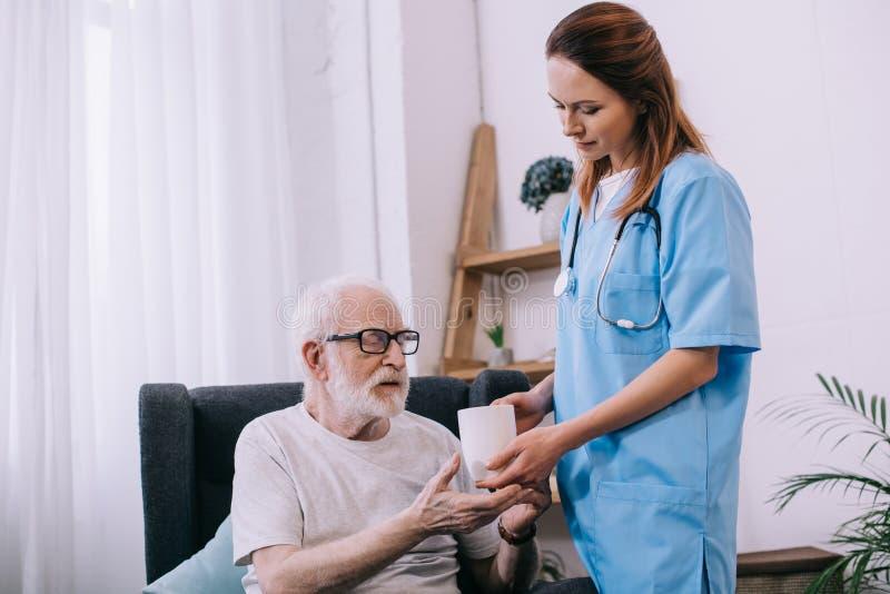 Infirmière aidant le patient supérieur à se tenir image stock
