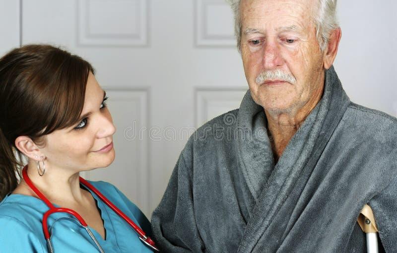 Infirmière aidant un aîné sur sa béquille images libres de droits