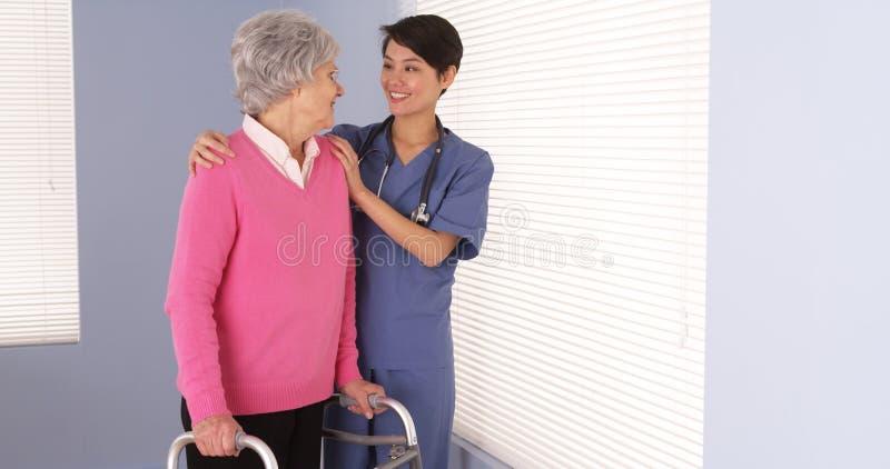 Infirmière aimable et parler se tenant prêt patient plus âgé de fenêtre photos libres de droits
