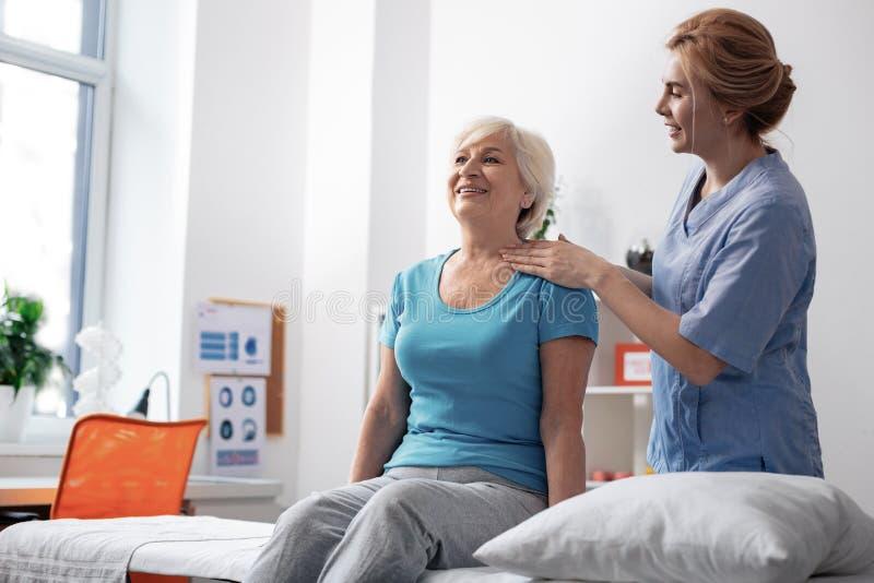 Infirmière amicale positive regardant son patient féminin photographie stock libre de droits