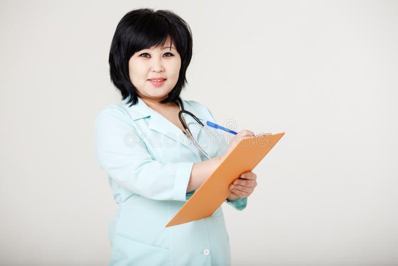 Infirmière asiatique de brune avec le stéthoscope autour du cou photographie stock libre de droits