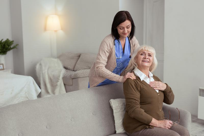 Infirmière attentive massant le dos de femme plus âgée photographie stock