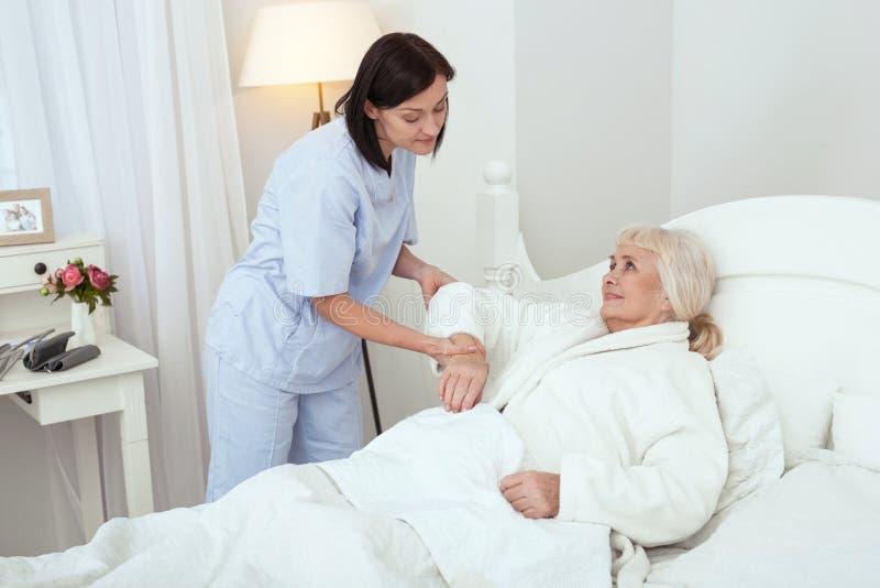 Infirmière attentive soulageant une dame plus âgée photographie stock