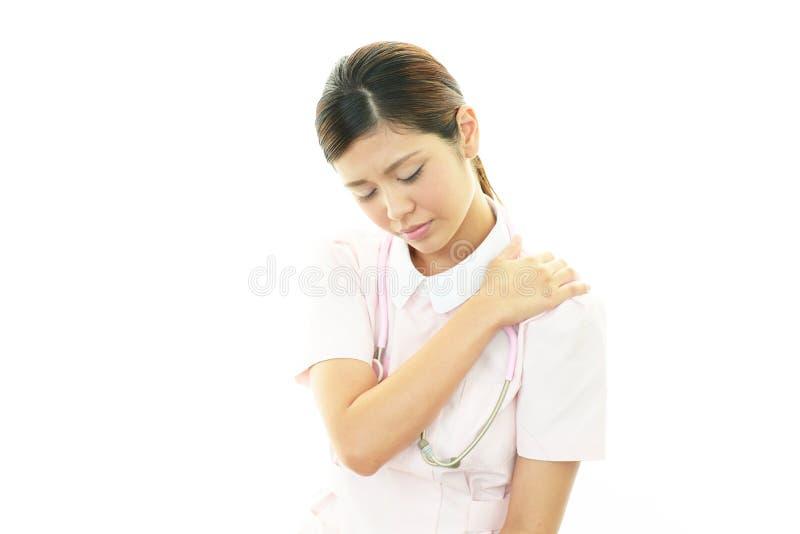 Infirmière avec douleur d'épaule. images libres de droits