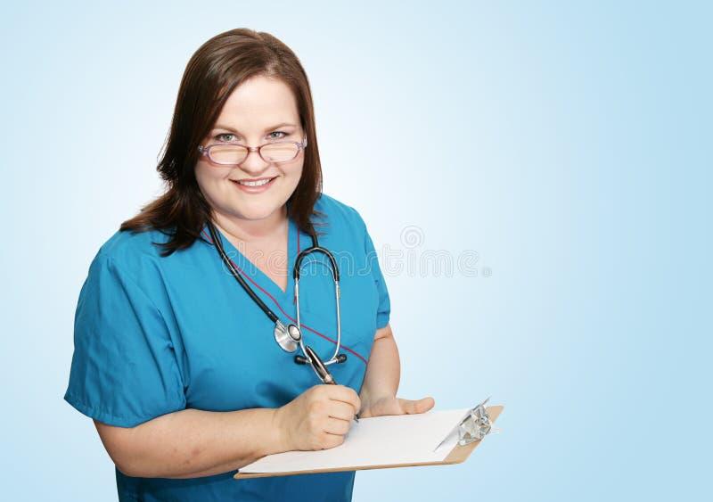 Infirmière avec la planchette sur le bleu image libre de droits