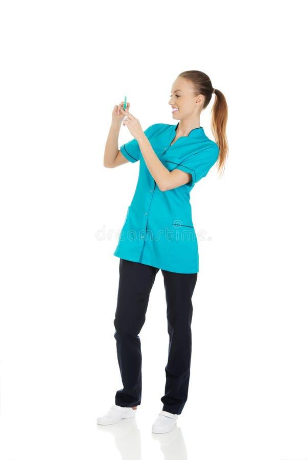Infirmière avec une seringue à disposition photographie stock