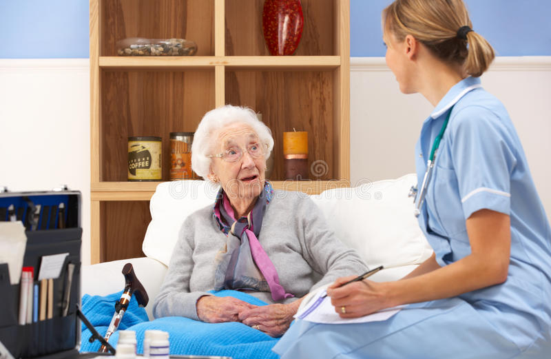 Infirmière BRITANNIQUE rendant visite au femme aîné à la maison photos libres de droits