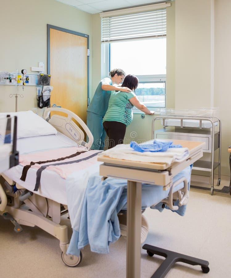 Infirmière Comforting Pregnant Woman à la fenêtre dedans photographie stock libre de droits