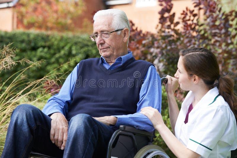 Infirmière Comforting Senior Man dans le fauteuil roulant photo stock