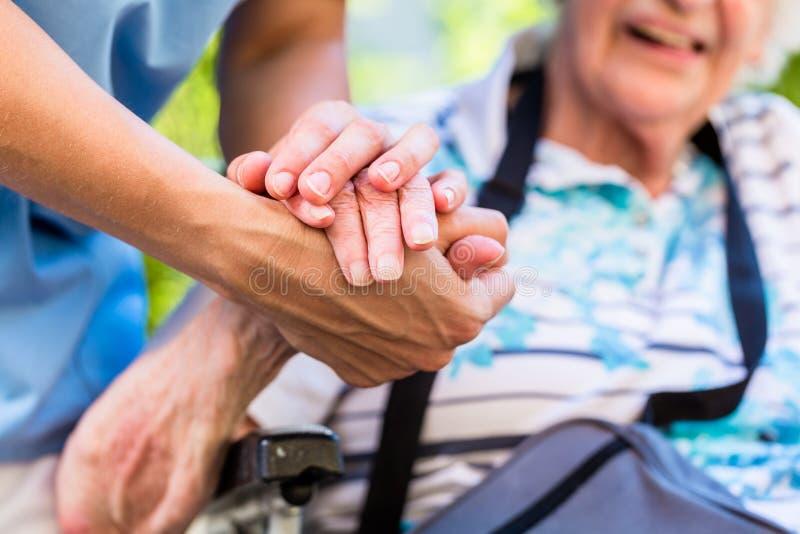 Infirmière consolant la femme supérieure tenant sa main images stock