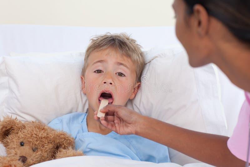 Infirmière contrôlant la gorge de petit garçon dans l'hôpital images stock