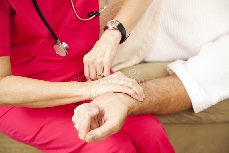 Infirmière de santé à la maison - prise de l'impulsion image stock