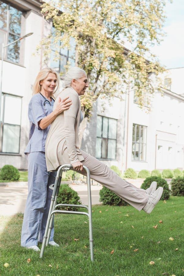 infirmière de sourire soutenant le patient supérieur s'exerçant avec le marcheur photo libre de droits